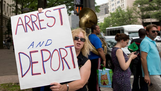 A woman holds up a sign across the street from a protest July 9 against Republican presidential candidate Donald Trump's portrayal of Mexican immigrants as criminals outside the new Trump hotel, in Washington.