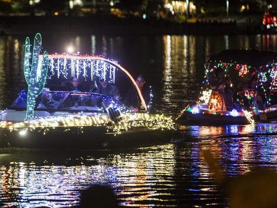 Boats lit up by Christmas lights and decorations make their way through Tempe Town Lake during Tempe?s Fantasy of Lights boat parade on Dec. 10.