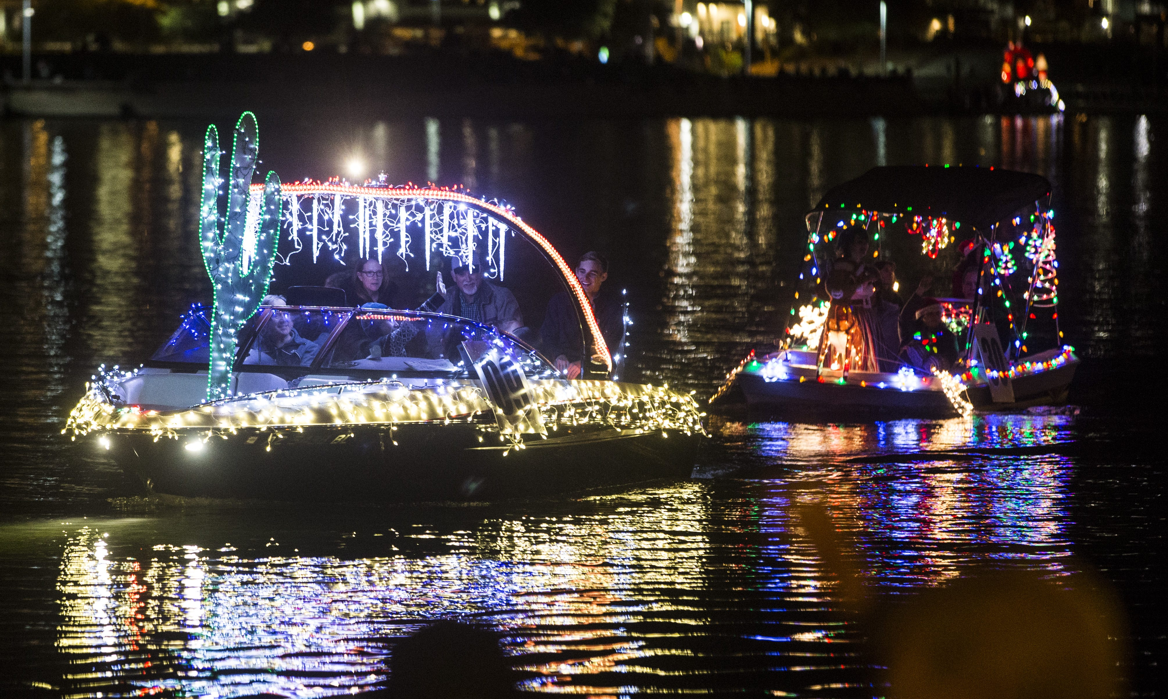 Boats lit up by Christmas lights and decorations make their way through Tempe Town Lake during & Tempe Fantasy of Lights boat parade 2017 azcodes.com