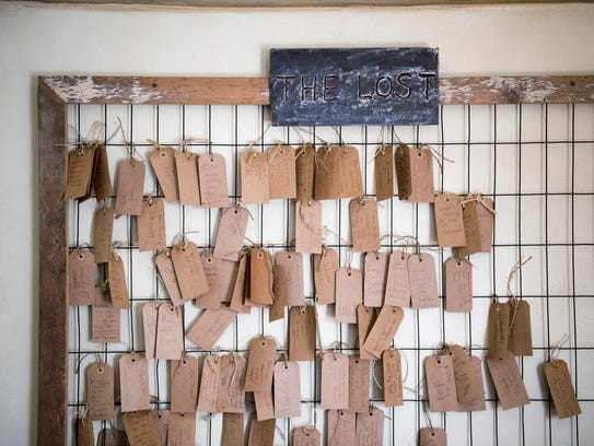 """Tags hanging in a prayer room represent """"the lost,"""" each with the name of someone whose family members wish would get help."""