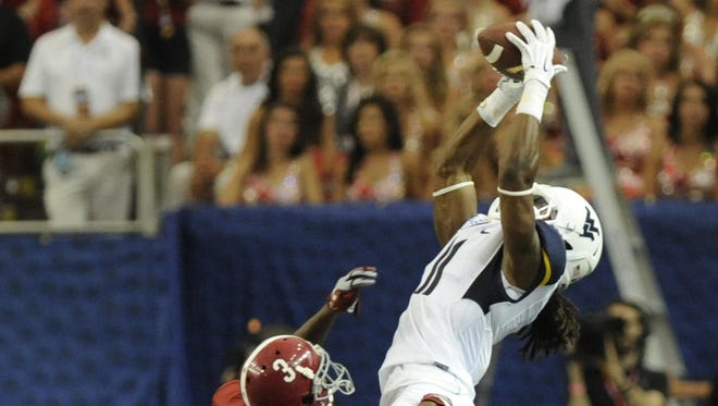 West Virginia wide receiver Kevin White catches a pass over Alabama defensive back Bradley Sylve last season.
