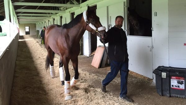 Kentucky Derby favorite Nyquist arrives to his barn at Churchill Downs with trainer Doug O'Neill.