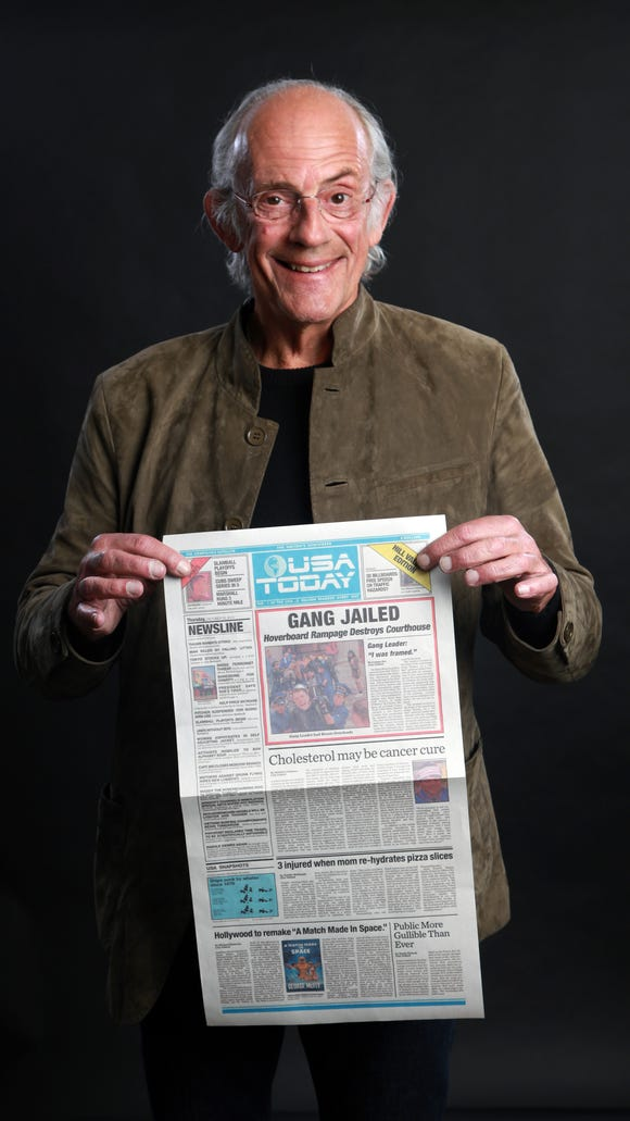Christopher Lloyd holds up a replica of the prop USA