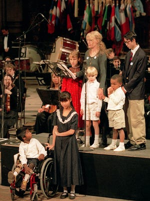 Mia Farrow in 1995 with her children, from left, front row; Thaddeus, Tam, second row; Eliza, Farrow, Sheamus, Isaiah,  and Moses.