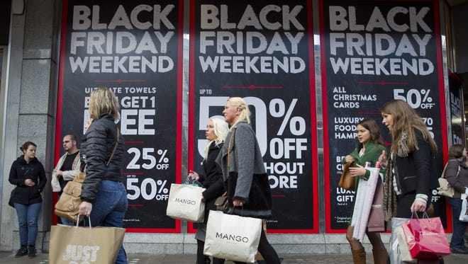 "Shoppers are pictured walking past 'Black Friday' advertising in shop windows on Oxford Street in central London on November 28, 2014. Police blasted stores for bringing ""Black Friday"" to Britain, with the US sales event descending into chaotic fist fights as frenzied consumers battled to grab discounted goods. In scenes of pandemonium around the country, common civility went out the window as yelling customers punched it out in a bid to secure reduced-price televisions and coffee makers. AFP PHOTO/JUSTIN TALLIS        (Photo credit should read JUSTIN TALLIS/AFP/Getty Images)"