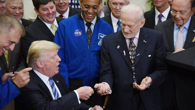 President Trump  gives a pen to Apollo 11 astronaut Buzz Aldrin after signing an executive order to reestablish the National Space Council in the Roosevelt Room of the White House Friday.