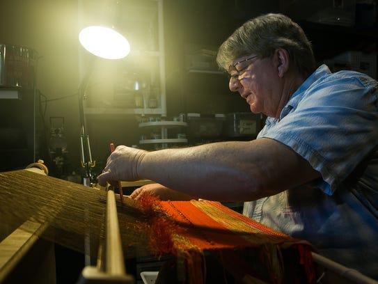 Steve Bailey works on his loom in his home studio.