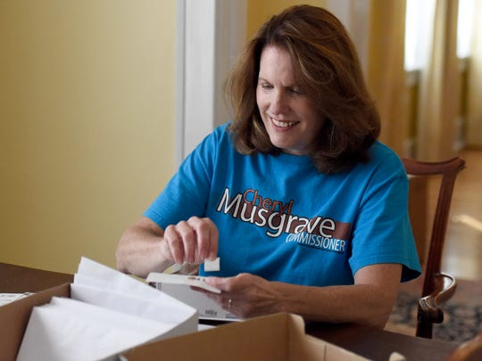 Vanderburgh County Commissioner candidate Cheryl Musgrave puts stamps on envelopes while working out of her home in Evansville recently.  Musgrave is currently mailing several hundred letters a day out to voters.