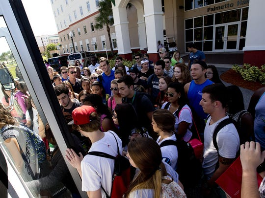 FGCU students prepare to board a shuttle bus heading to the main campus from the South Village dorms.