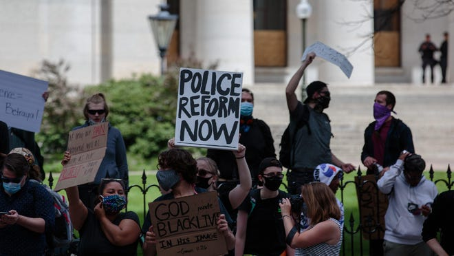 """A protester holds a sign that reads """"Police Reform Now"""" as protests continue following the death of Minneapolis resident George Floyd on Monday, June 1, 2020 in Columbus, Ohio. Floyd, a 46-year-old black man, was killed while in police custody after allegedly passing a counterfeit $20 bill at a conveinence store. Derek Chauvin, one of four Minneapolis police officers involved in Floyd's arrest, has himself been arrested and charged with third-degree murder and manslaughter. During the arrest, video footage showed Chauvin kneeling on Floyd's neck for almost nine minutes as Floyd repeatedly said """"I can't breathe."""""""
