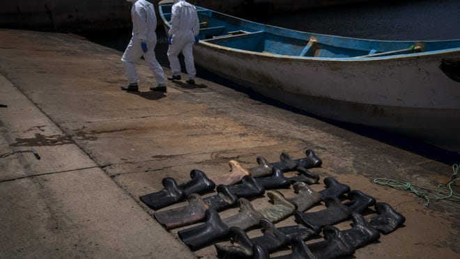 Waterproof boots are placed on the ground by police officers as they inspect a boat where 15 Malians were found dead adrift in the Atlantic on Thursday, Aug. 20, 2020 in Gran Canaria island, Spain.