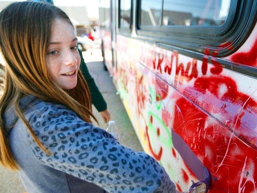 Lily Derthick paints an arrow on the side of the bus.