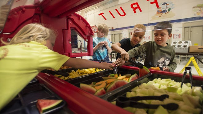 First graders Gabriel Medina, right, and Cameron May, center, grab fruit while Jakob Bouska, left, tries to reach the tongs on Tuesday, April 10, 2018, at Riffenburgh Elementary School in Fort Collins, Colo.