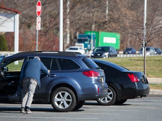 A man stretches out next to his car as he makes a rest stop at the Delaware Welcome Center Travel Plaza along I-95.