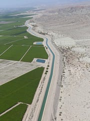 The Coachella Canal snakes between open desert and agricultural fields near the northern end of the Salton Sea.