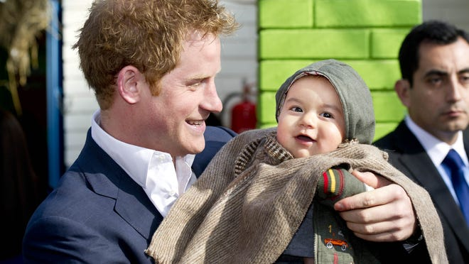Prince Harry holds young Matias Gonzalez during visit to kindergarten for indigenous children on June 27, in Santiago, Chile.