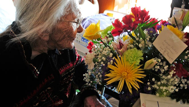 Esther Haskins enjoys the fragrance from a bouquet of flowers delivered to her hospital room on her 102nd birthday last week.