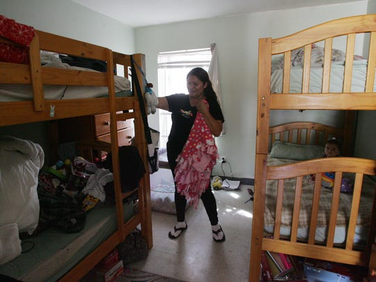 Albertina Ramirez tidies her room at the Salvation Amy transitional living center in Ventura. Ramirez shares the room with her 9-month-old daughter Laura Juarez (right) and her two other children.