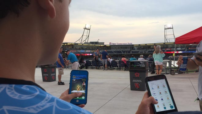 Thirteen-year-old Reed Sculley and 16-year-old Cameron Keener play Pokemon Go on Friday at First Tennessee Park.