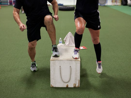 Kevin and Cathy Kansman utilize a box to do step-ups during their workout.