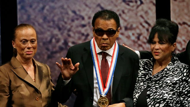 In this Sept. 13, 2012 file photo, boxing great Muhammad Ali, center, waves alongside his wife Lonnie Ali, left, and his sister-in-law Marilyn Williams, right, after receiving the Liberty Medal during a ceremony at the National Constitution Center in Philadelphia.