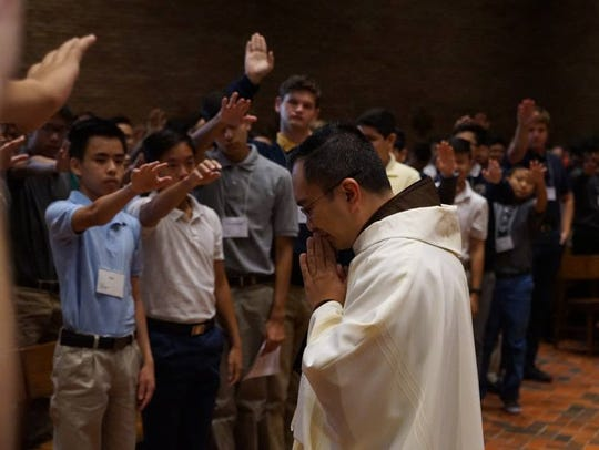 "Students extend their hands over the Rev. Zoilo ""Zoy"""