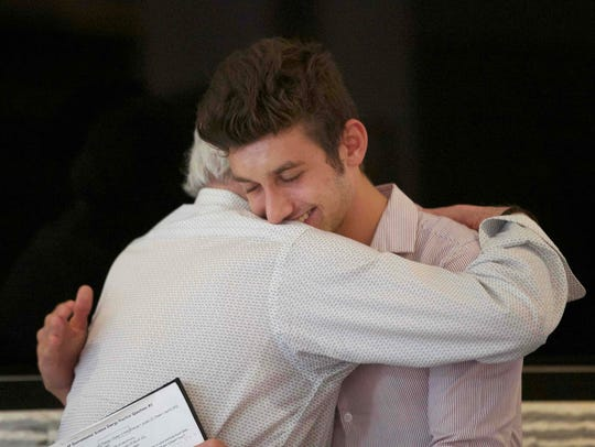 Drew Principe, right, and Henry Oster share a hug at