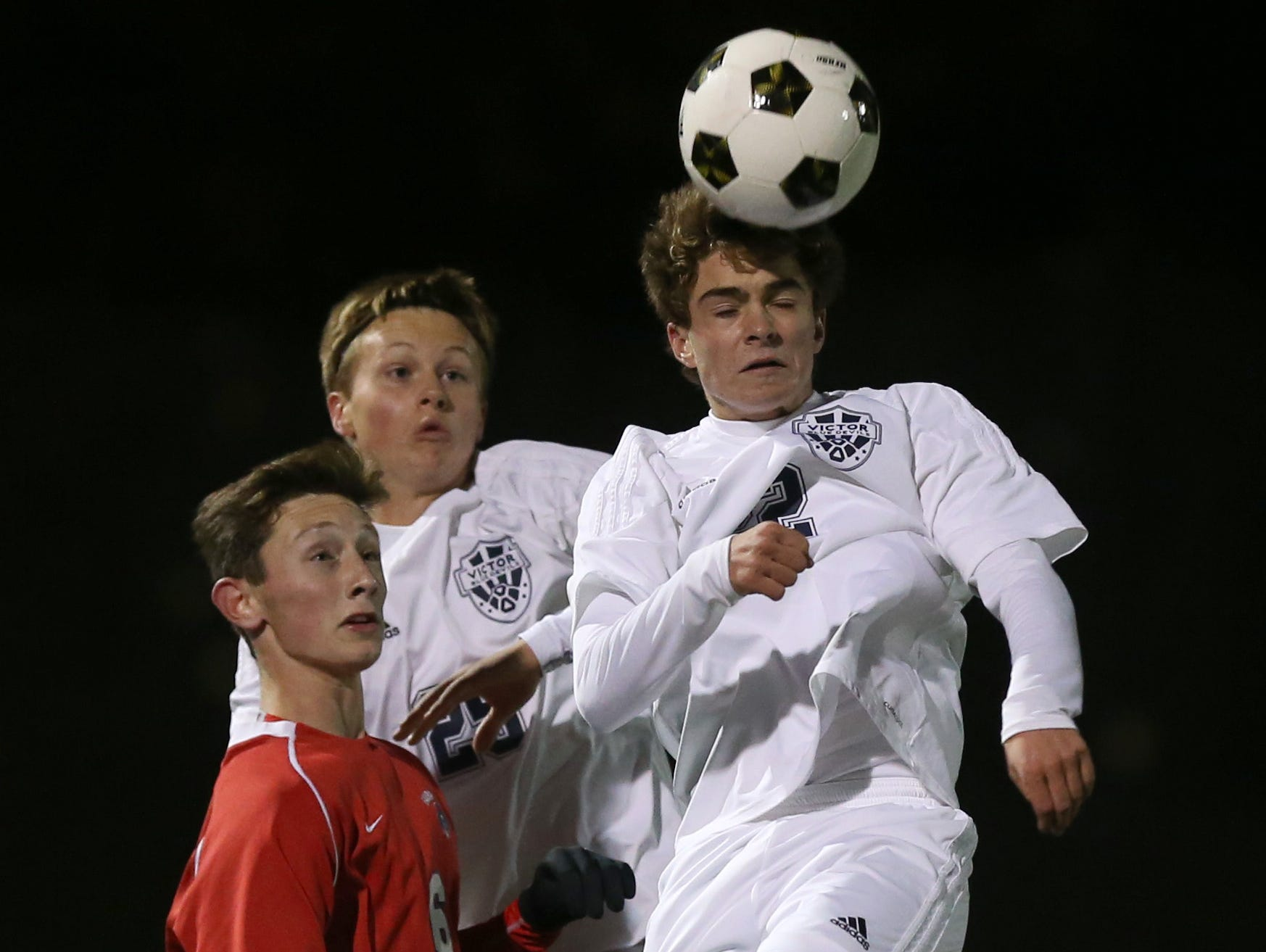 Victor's Spencer Ryczek gets his head on the ball ahead of pressure by Fairport's Nick Guida during their Class AA semifinal game at Spencerport Thursday, Oct. 29, 2015.