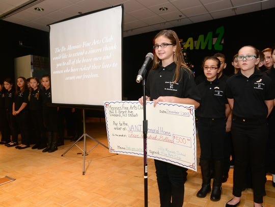 Fifth-grade student Kylee Reissek, 10, presents a check