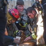 Firefighters from the Department of the Navy and Escambia Fire and Rescue revive a dog suffering from smoke inhalation after it was rescued from a house fire on Alton Road in Warrington Friday afternoon. The firefighters efforts to save the animal were successful.