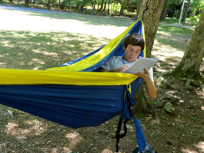 Camp participant Tanner Shultz, 17, of South Carolina chooses to spend his free time working in the comfort of a hammock at Nature Camp near Vesuvius on Wednesday, June 25, 2014.