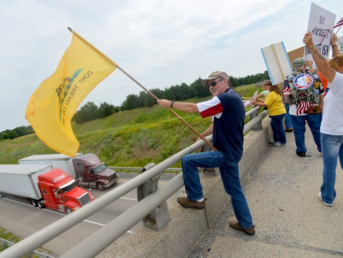 "Terry Adams of Churchville holds onto a ""Don't Tread On Me"" flag. He joins about 50 people who came to the Va. 612 overpass in Verona on Saturday morning, July 19, 2014. They gather to demonstrate for and against various immigration issues, drawn by news that an Augusta County center hosts several undocumented children."
