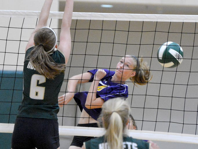 Waynesboro's Alyssa Balsley hits the ball into the net as Wilson Memorial's Emma Hilbert was ready to try to block during a volleyball game played in Fishersville on Tuesday, Sept. 2, 2014.