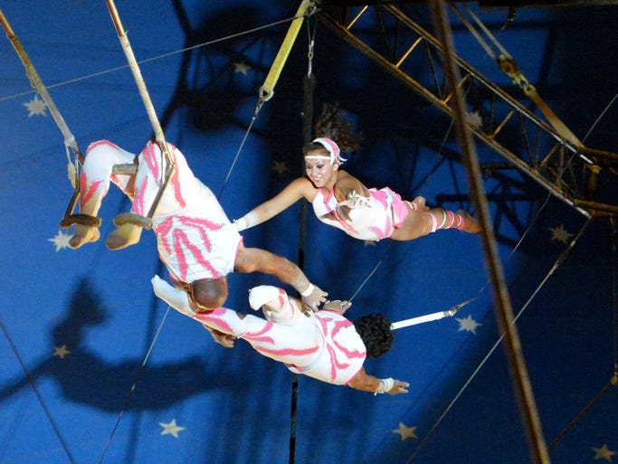 Trapeze artists perform for the crowd under the big top for Cole Brothers Circus at Augusta Expo in Fishersville on Tuesday, Sept. 2, 2014. The circus continues through Thursday.