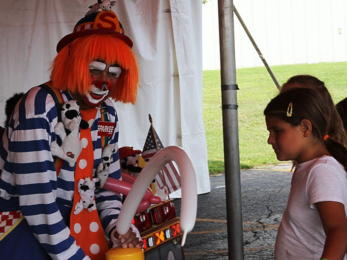 Sparkee the clown makes a ballon hat for a couple of girls at the Winnebago County Fair on Thursday.