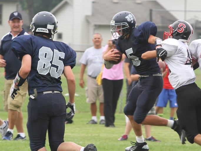 Valley Christian's Ryan Van Maanen fights off Sevastopol's Quin Schram Saturday in eight man football game.