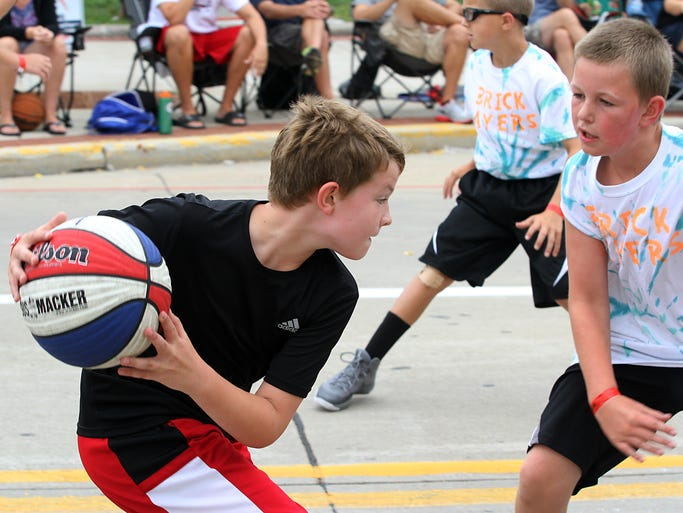 A Pointer player tries to get around a Brick Layer as Main Street in Oshkosh hosted the three on three Gus Macker Basketball Tournament over the weekend.