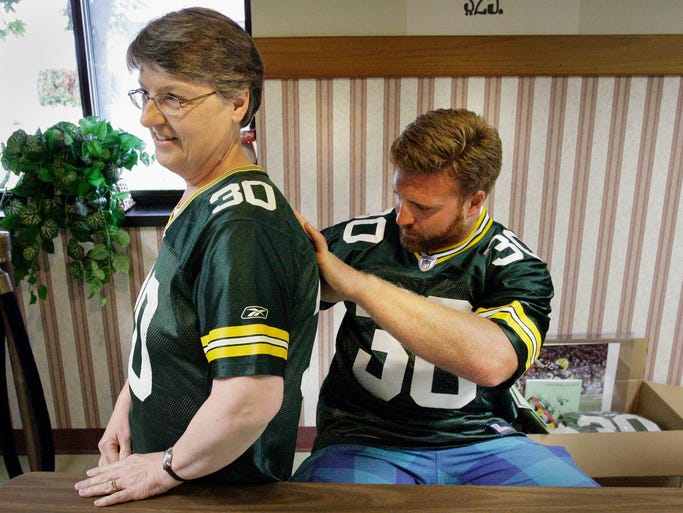 """Green Bay Packer John Kuhn (30) signs the back of a jersey being worn by Carol """"Kuhn"""" Brott  of Plymouth Tuesday July 8, 2014 at Range Line Inn in Kohler.  Brott says her maiden name was Kuhn."""
