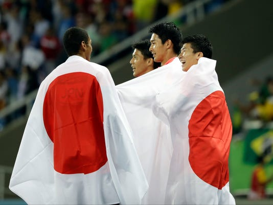 The Japan team celebrate winning the silver medal in the men's 4x100-meter relay final during the athletics competitions of the 2016 Summer Olympics at the Olympic stadium in Rio de Janeiro, Brazil, Friday, Aug. 19, 2016. (AP Photo/David J. Phillip)