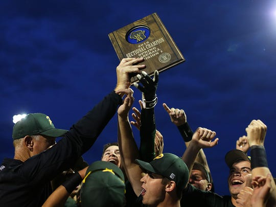 Green Bay Preble head coach Andy Conard hoists the WIAA Division 1 sectional award after the Hornets defeated Green Bay West/East in Tuesday's sectional finals at Bay Port. See more photos from the game at greenbaypressgazette.com.