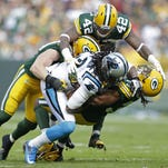 Carolina Panthers wide receiver Kelvin Benjamin is brought down by Tramon Williams, A.J. Hawk and Morgan Burnett in the second quarter.