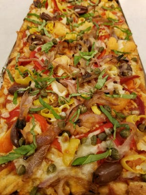 Pizza al Taglio is baked in a rectangular tray and topped with plenty of color.