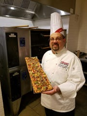 Chef Anthony Legname holds a Pizza al Taglio he made.