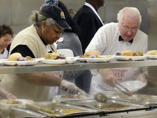 Ed Gray, right, serves a meal at the Waterfront Rescue