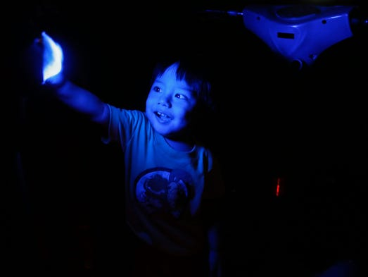 A Filipino boy plays with available light from an amusement