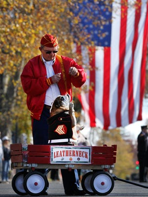 Retired Marine Sgt Ben Warner, Lansdale, PA, coaxes his English Bulldog 'Segeant Leatherneck' to salute during the National Anthem during the Toms River Veterans Day parade Monday, November 14, 2016.