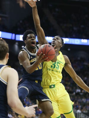 Michigan Wolverines guard Derrick Walton Jr. drives against Oregon forward Kavell Bigby-Williams during the first half Thursday, March 23, 2017 at the Sprint Center in Kansas City in the NCAA tournament.