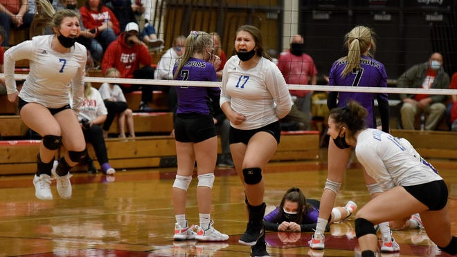 Nadia Papalas, Allyson Dillon and Madison Wiseman of Carlson celebrate after coming from behind to beat Woodhaven in the fifth game of the Division 1 District semifinals Wednesday night. On the other side of the net, Woodhaven's Lauren Ray lies on the floor in disbelief between teammates Miyana Dishroon and Syndey Mariewitz.