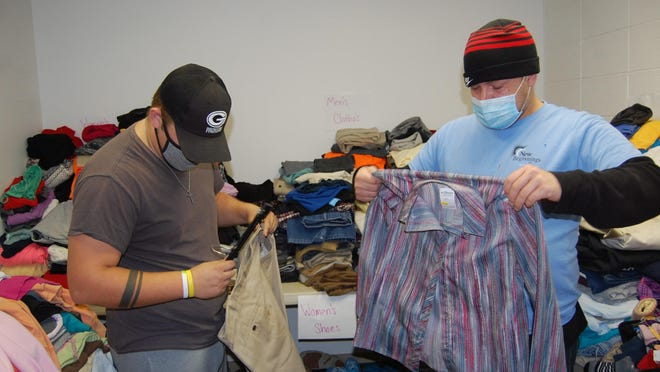 Trey McKee, left, and Gary Race sort and fold donated clothing that New Beginnings Inc. hopes to give away to those in need through a downtown storefront. Besides winter clothing, the agency has received a lot of dress clothes available for free to those in need.