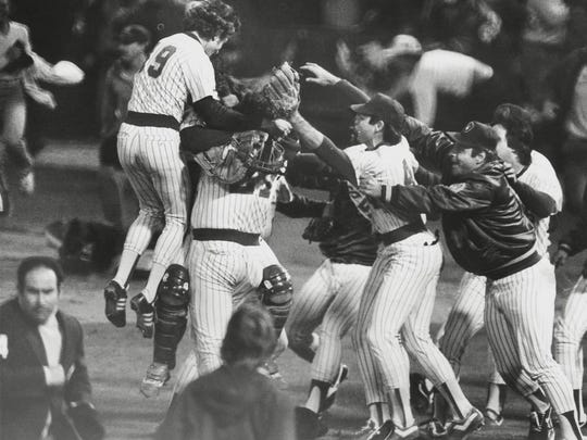 Brewers players celebrate after beating the California Angels to win the 1982 American League pennant as fans storm the field at County Stadium.